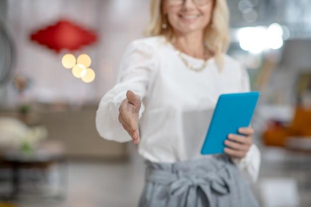 はじめまして。挨拶のために伸ばしたスリムな優雅な女性の手、タブレットで立っている女性、顔は見えません。