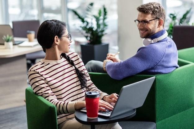 Приятно с вами познакомиться. удивительная длинноволосая девушка поворачивает голову во время разговора со своим коллегой