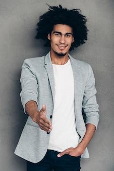 만나서 반가워! 당신에게 인사하기 위해 손을 내밀고 있는 쾌활한 젊은 아프리카 남자