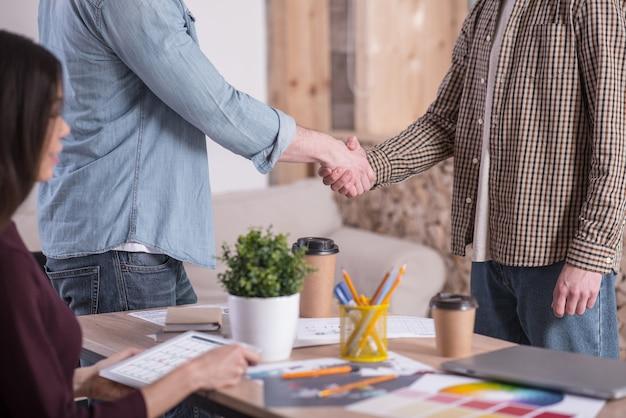 Рад встрече. крупным планом - дружеское рукопожатие между двумя позитивными приятными людьми при встрече