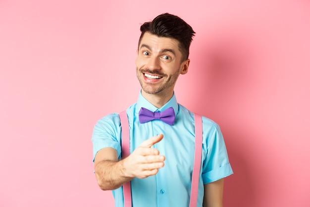 始めまして。ハンサムな若い男は握手のために手を伸ばし、フレンドリーで礼儀正しい笑顔で、ピンクの背景の上に立って自己紹介します。