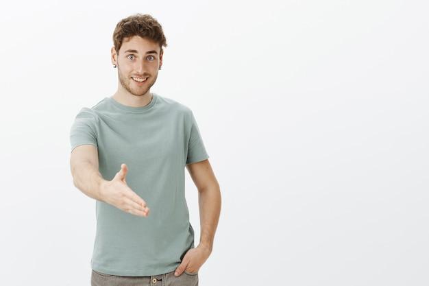 Приятно познакомиться, надеюсь ладить. портрет дружелюбного счастливого молодого человека в повседневной футболке