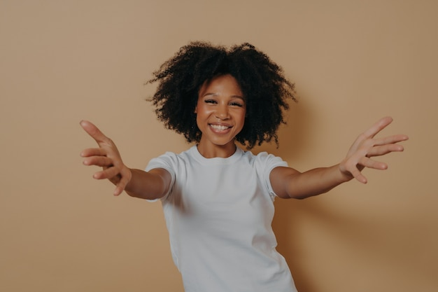 만나서 반갑습니다. 베이지색 배경에 격리된 채 손을 벌리고 흰색 티셔츠를 입은 친절한 긍정적인 여성이 사람을 안고 싶어하는 20대 행복한 아프리카 여성. 초대 개념