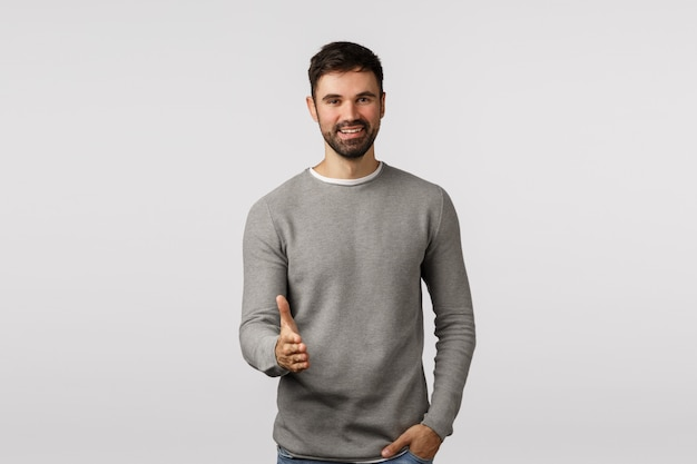 はじめまして、喜んでビジネスを行います。フレンドリーで見栄えがよく、積極的な男性起業家のカジュアルな服装、握手と笑顔のために腕を伸ばし、こんにちはまたはこんにちは