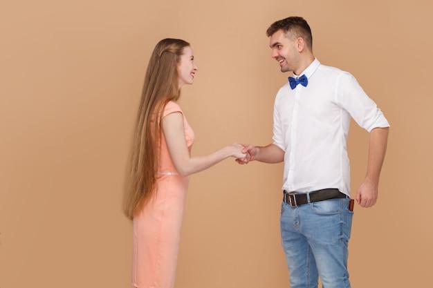Рад встрече. рукопожатие вида сбоку профиля красивого человека в белой рубашке и блондинке с длинными волосами в розовом платье, смотрящей с зубастой улыбкой. закрытый студийный снимок, изолированный на светло-коричневом фоне