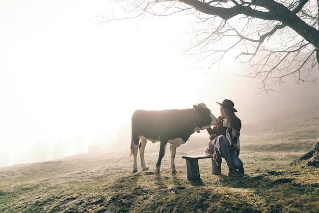 만나서 반갑습니다. 산 벤치에 앉아 있는 동안 소를 만지고 담요로 덮인 젊은 여자
