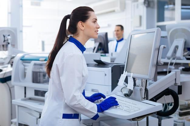 Приятное прикосновение. энергичная положительная женщина-лаборант смотрит на экран и печатает, стоя возле медицинского оборудования