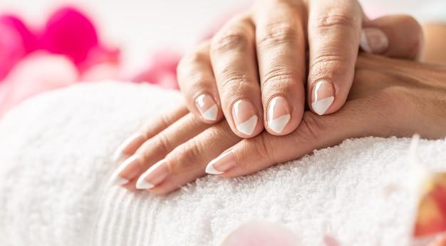 Красивые неокрашенные ногти скрещенных рук на белом полотенце в маникюрном салоне.