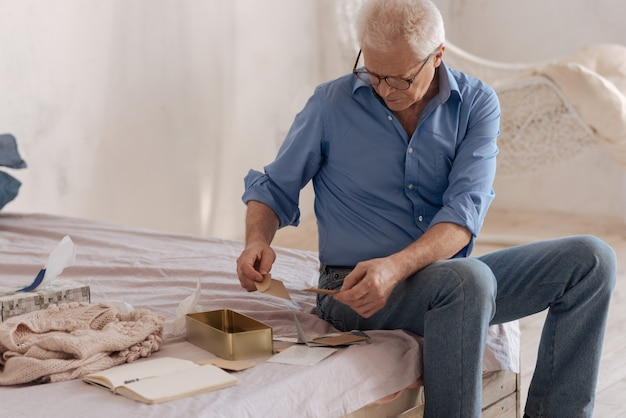 Nice unhappy senior man holding envelopes and looking at his old mail while remembering his past