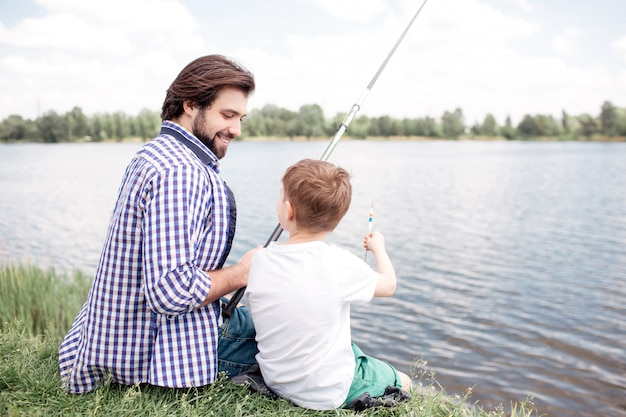Nice view of happy son and dad sitting together at river shore. guy is looking at his son and fishing. boy is looking at his father and talking to him.