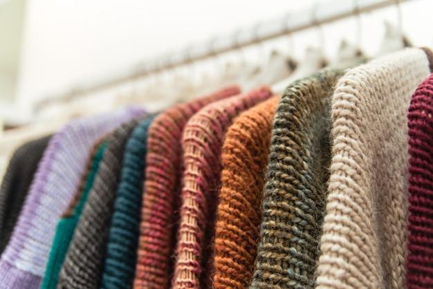 Красивые теплые красочные свитера висят на вешалках внутри торгового центра.