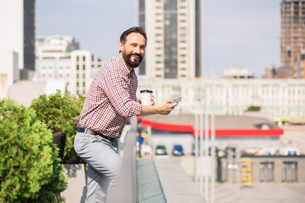 いい天気。屋上に立っている間彼のスマートフォンを使用して陽気なhandsoemビジネスマン