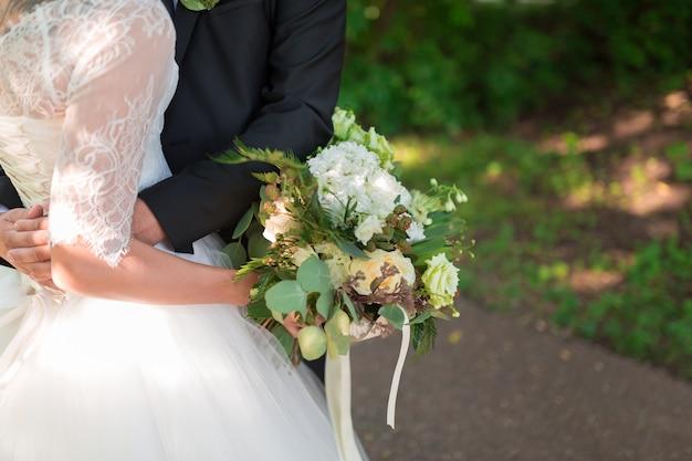 Nice wedding bouquet in bride and groom hand