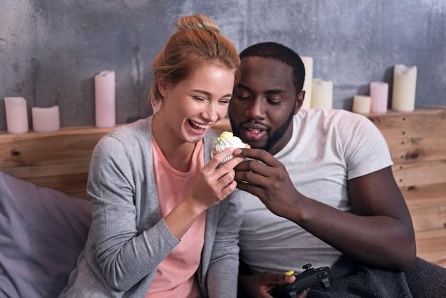 Хорошие выходные. счастливая пара молодых геймеров ест кексы, лежа в спальне и используя консоль.