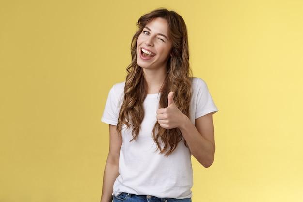 잘했어 친구. 쾌활한 나가는 건방진 매력적인 곱슬 머리 여성 윙크 웃는 끄덕 승인 당신의 선택처럼 엄지 손가락을 보여줍니다 좋은 직업 수락 조건 스탠드 노란색 배경