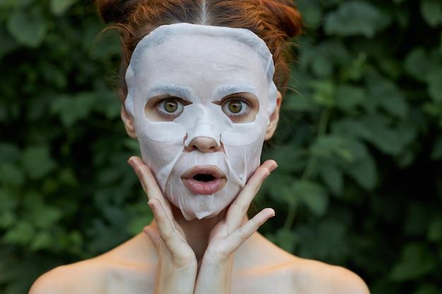 素敵な女性アンチエイジングマスクあなたの手であなたの顔に触れてください美容緑の茂み