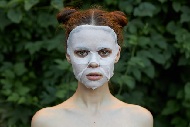 Nice woman anti-wrinkle mask bare shoulders green bushes