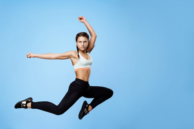 Nice woman in cool sportswear jumping high with hands up on blue