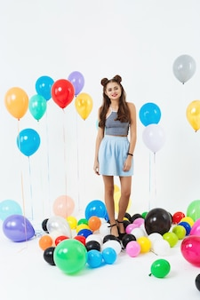 Nice woman in cool summer outfut posing with balloons