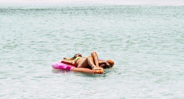 ビーチの海水で日光浴を楽しんでいる素敵な女性