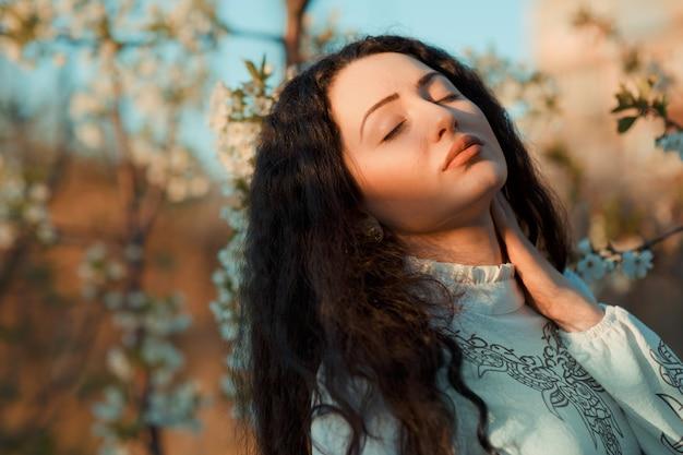 3 월에 벚꽃이 피는 동안 태양의 온기를 즐기는 좋은 여자