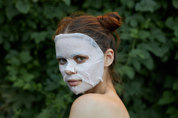 Nice woman face mask dermatology green leaves in the space model portrait side view.