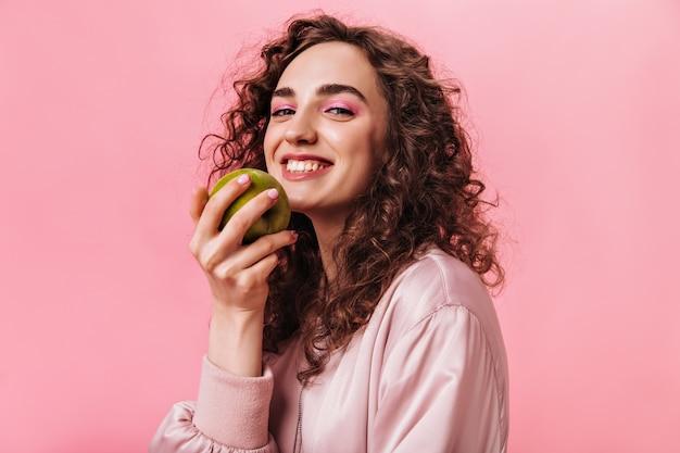 Красивая женщина в хорошем настроении держит зеленое яблоко на розовом фоне