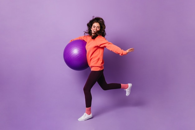 Nice woman in pink socks, orange sweatshirt and dark leggings runs on purple wall with fitball