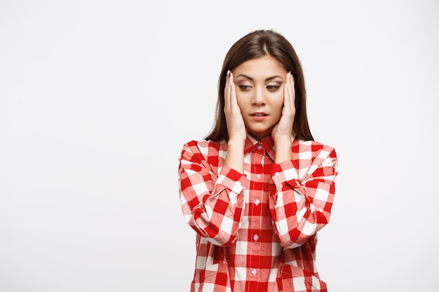 Nice woman in red and white shirt having headache