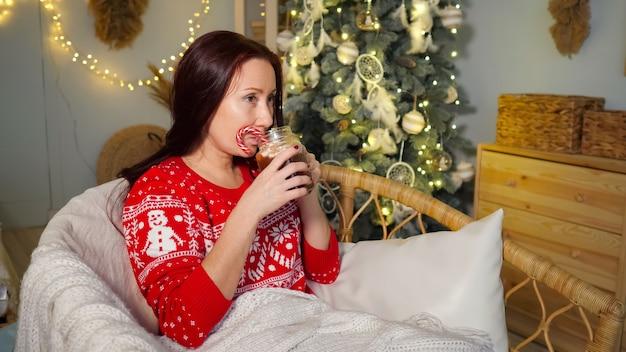 Симпатичная женщина сидит в кресле и пьет напиток