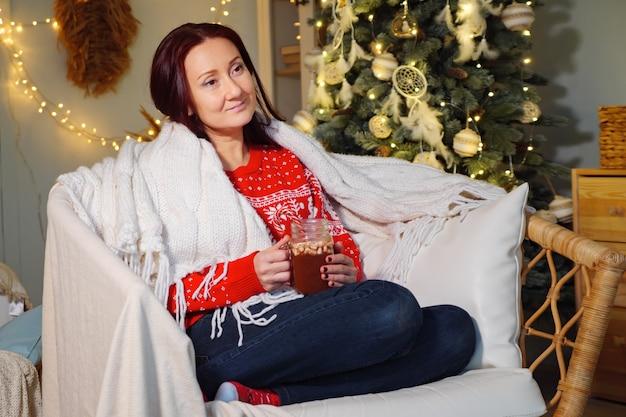 Симпатичная женщина сидит в кресле, заворачивая плед и пьет напиток