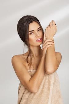 Bella donna in morbido asciugamano da bagno applicando la crema nelle mani, guardando dritto