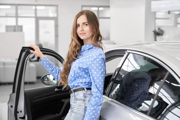 Nice woman standing near new white car in auto salon