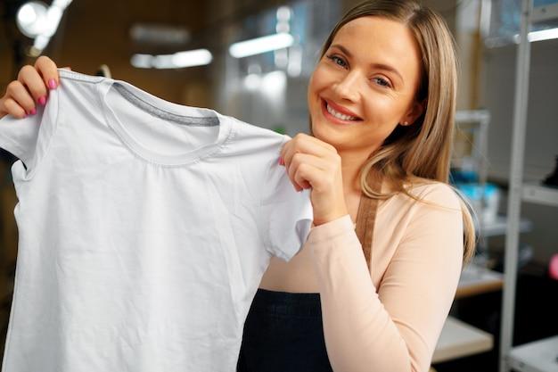Милая женщина портной держит только что сшитую футболку