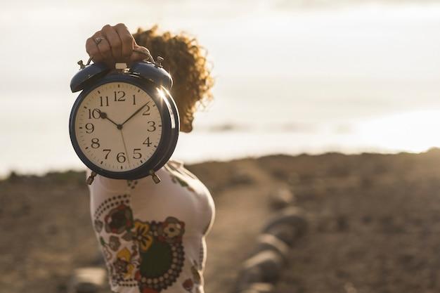 Милая женщина берет большие часы-будильник старый и старинный под рукой, показывая вам минуты и секунды. спешка и вневременная концепция. время заката на открытом воздухе