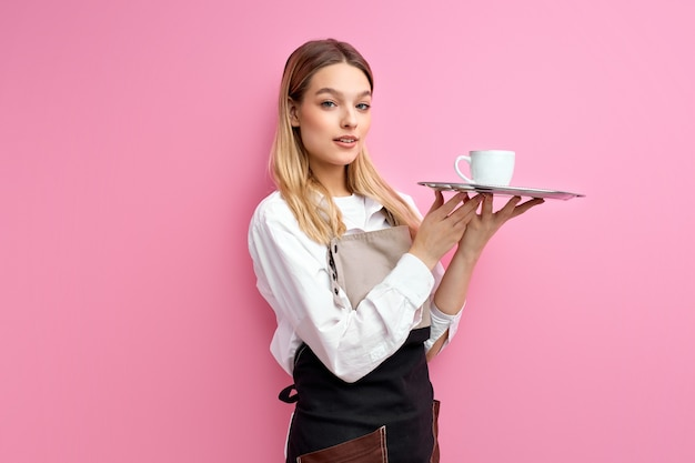 Nice woman waitress in apron, offering cup of delicious tasty coffee, stand looking at camera, friendly staff of cafe restaurant.