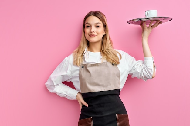 Nice woman waitress in apron, offering cup of delicious tasty coffee on tray, stand smiling
