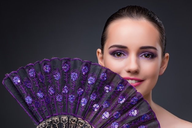 Nice woman with fan against gray background