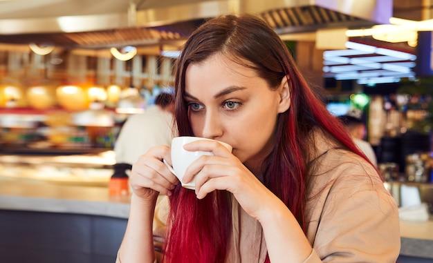 赤い染めの髪の素敵な女性がレストランでコーヒーを持っています