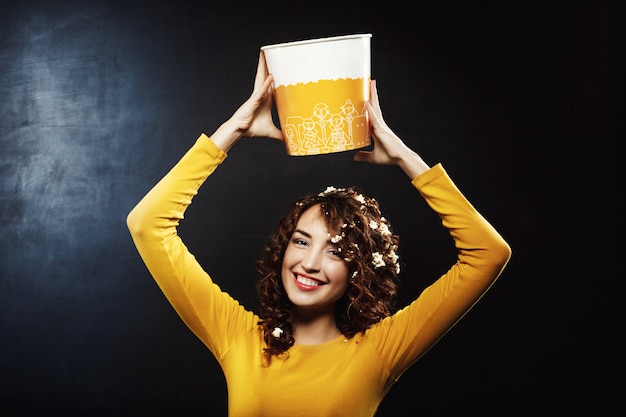 Nice woman in yellow sweatshirt holding popcorn bucket up, smiling