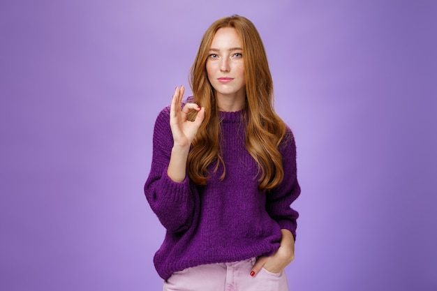Nice work, cool. portrait of delighted stylish and confident good-looking redhead female in purple sweater showing ok gesture as reacting to excellent job, proud of friend over violet wall.