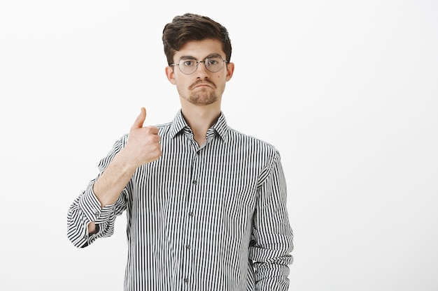 Хороший рабочий человек. доволен впечатленным привлекательным учеником в очках, показывающим большие пальцы вверх и сосущим губы, одобряющим и одобряющим идею или проект друга, делясь своим мнением через серую стену