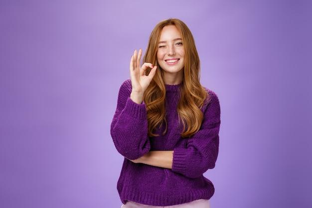 수고하셨습니다. 보라색 스웨터를 입은 만족스럽고 단호하고 지지적인 빨간 머리 여성은 보라색 벽 너머로 제품을 좋아하며 괜찮은 제스처를 보여주며 승인을 위해 윙크를 하고 웃고 있습니다.