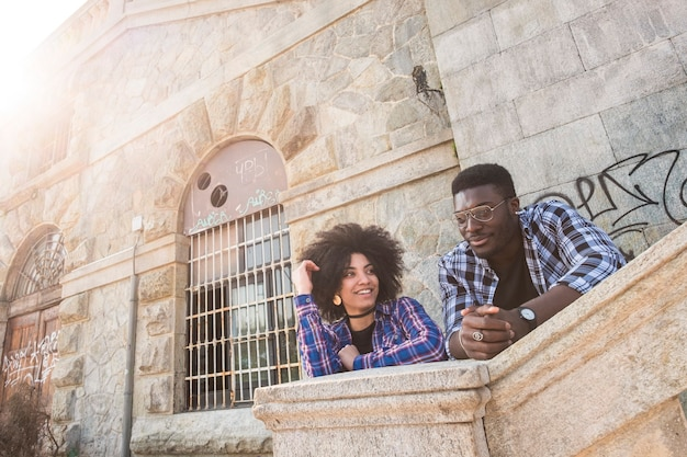 素敵な若い美しい陽気な黒人のアフリカ人種のカップルは、古代の建物の都会の場所で都市のレジャーアウトドール活動を楽しんでいます。楽しんで、友情を楽しんでください。夏の晴れた日