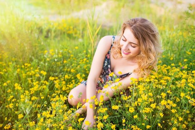 Милая молодая красивая женщина в платье летом в лесу в солнечный теплый день во время отпуска