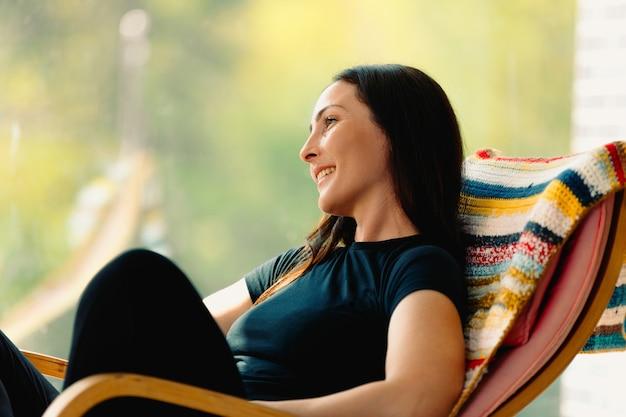 Симпатичная молодая брюнетка с яркой улыбкой наслаждается прекрасным днем, сидя в кресле-качалке.