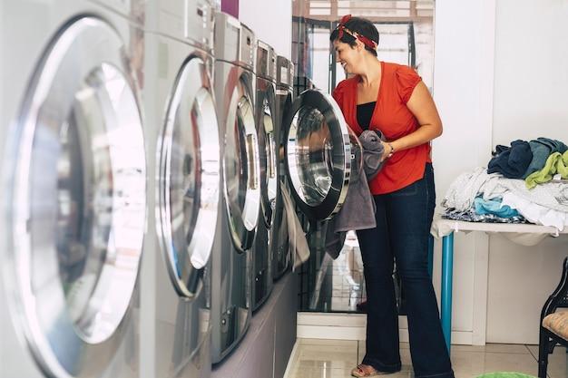 Милая молодая брюнетка стирает и чистит некоторые платья и одежду в автомате для стирки ковриков. деловая активность для людей, у которых мало времени и стресса. городской магазин