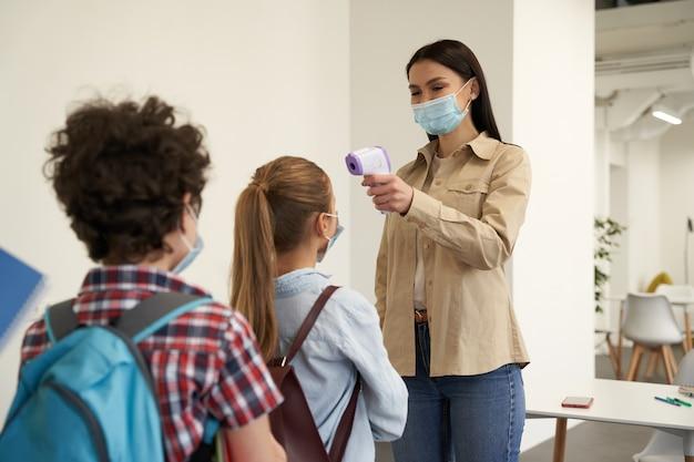보호 마스크를 쓴 멋진 젊은 여교사가 학교 아이들을 선별하는 동안 웃고 있습니다.