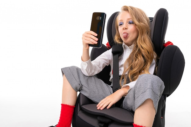 Nice young girl dressed in a classic style with red socks sitting in a child's car seat showing her tongue while looking at the phone