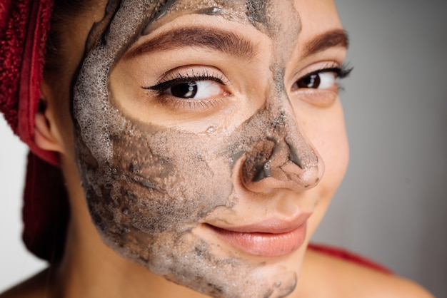 A nice young girl has applied a useful clay mask to half the face, wants to be beautiful